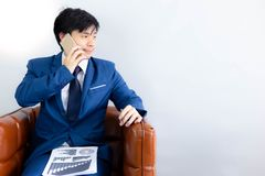 Przystojny biznesowego mężczyzny spojrzenie przy kopii przestrzenią podczas używać telefon dla obraz stock