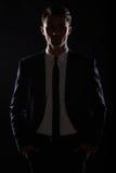 Przystojny biznesowy mężczyzna w czarnym apartamencie, backlight Fotografia Royalty Free