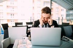 Przystojny biznesowy mężczyzna woking przy laptopem z kierowniczą obolałością w kawiarnia sklepie przy tarasem obrazy royalty free