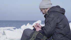 Przystojny blond brodaty mężczyzny obsiadanie wśród lodów pisze jego obserwacjach w notatniku Biegunowy badacz na lodowu zbiory