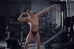 Przystojny bodybuilder pozuje w gym, perfect mięśniowy męski ciało Fotografia Stock