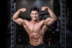 Przystojny bodybuilder szkolenie w gym mężczyzna dźwignięcia seksownych dumbbells Zdjęcie Stock