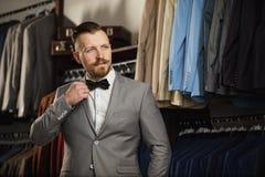 Przystojny brodaty biznesmen w klasycznym kostiumu Mężczyzna w klasycznej kamizelce przeciw rzędowi kostiumy w sklepie Obrazy Stock
