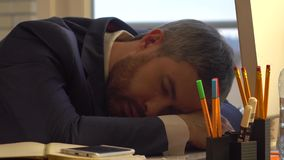 Przystojny brodaty biznesmena dosypianie w ranku przy jego miejscem pracy po pracować przez noc Zdjęcie Stock