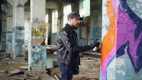 Przystojny brodaty facetów graffiti artysta maluje z kiści farby inside porzucającym budynkiem Nowożytna uliczna sztuka, młodość zbiory wideo