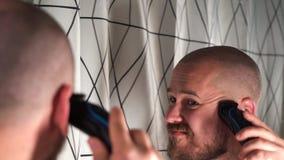 Przystojny brodaty faceta golenie z drobiażdżarką w łazience zbiory