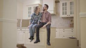 Przystojny brodaty mężczyzna i śliczny kobiety obsiadanie na stole w kuchni w nowym mieszkaniu Rodzina dyskutuje plany o nowym zdjęcie wideo