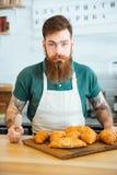Przystojny brodaty mężczyzna barista z croissants w sklep z kawą Zdjęcia Royalty Free