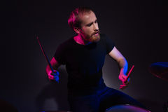 Przystojny brodaty mężczyzna dobosza obsiadanie i bawić się bębeny z drumsticks Fotografia Royalty Free