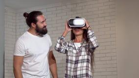 Przystojny brodaty mężczyzna ogląda jego dziewczyny używa rzeczywistość wirtualna szkła zdjęcie wideo