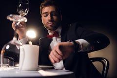 przystojny brodaty mężczyzna patrzeje zegarek podczas gdy czekający romantyczną datę zdjęcie stock