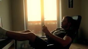 Przystojny brodaty mężczyzna relaksuje w domu i pisać na maszynie na jego smartphone zdjęcie wideo