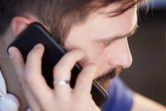 Przystojny brodaty mężczyzna używa mobilnego smartphone przy biurem zamazujący tło zdjęcia stock