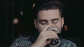 Przystojny brodaty mężczyzna w ciepłym pulowerze wznosi toast szkło wino, uśmiecha się je i pije, Mieć zabawę, robi grzance Jest zdjęcie wideo