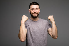 Przystojny brodaty mężczyzna w przypadkowych ubraniach podnosi ręki w pięściach, patrzejący kamerę i ono uśmiecha się Obraz Stock
