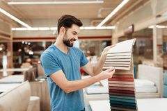 Przystojny brodaty mężczyzna wybiera kolor na kolor palecie Wybierać kolor materac na kolor palety przewdoniku Zdjęcia Stock
