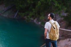 Przystojny brodaty mężczyzna z rękami w jego kieszeniach, patrzeje oddalonego trwanie pobliskiego jezioro Młody facet jest ubrany Obrazy Stock
