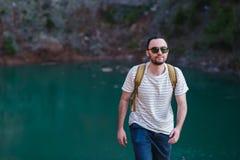 Przystojny brodaty mężczyzna z rękami w jego kieszeniach, patrzeje oddalonego trwanie pobliskiego jezioro Młody facet jest ubrany Fotografia Royalty Free