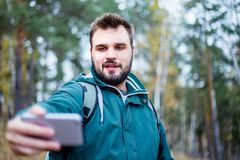 Przystojny brodaty męski turysta bierze selfie w lesie zdjęcia royalty free