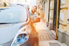 Przystojny brodaty młodego człowieka falowanie od jego samochodu Zdjęcia Stock