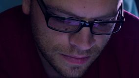 Przystojny brodaty młody człowiek w czarnych obręczy szkłach używać jego pastylka komputer w ciemnym pokoju Purpura ekranu łuna Fotografia Royalty Free