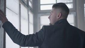 Przystojny brodaty młody człowiek z poważną twarzą dotyka szkło okno