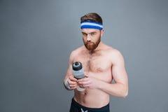 Przystojny brodaty młody sportowiec z butelką woda zdjęcia stock