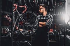 Przystojny brodaty m??czyzna w szk?ach stoi blisko niezmiennego bicyklu przy jego sw?j warsztatem zdjęcia stock