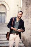 Przystojny brodaty mężczyzna patrzeje kamerę podczas gdy trzymający jego telefon Fotografia Stock