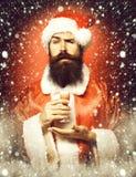 Przystojny brodaty Santa Claus mężczyzna trzyma szkło alkoholiczka strzał na ręce w bożych narodzeniach z długą brodą na poważnej obraz royalty free