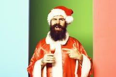 Przystojny brodaty Santa Claus mężczyzna trzyma szkło alkoholiczka z długą brodą na śmiesznej twarzy strzelał w czerwonych bożych zdjęcie royalty free
