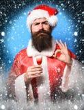 Przystojny brodaty Santa Claus mężczyzna trzyma szkło alkoholiczka z długą brodą na śmiesznej twarzy strzelał w czerwonych bożych zdjęcia stock