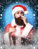 Przystojny brodaty Santa Claus mężczyzna trzyma szkło alkoholiczka z długą brodą na zadowolonej twarzy strzelał w czerwonych boży obrazy royalty free