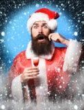 Przystojny brodaty Santa Claus mężczyzna trzyma szkło alkoholiczka z długą brodą na zdziwionej twarzy strzelał w bożych narodzeni fotografia stock