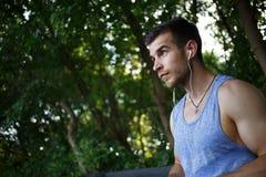 Przystojny brunetka mężczyzna słucha muzyka na hełmofonach obraz stock