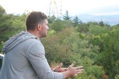 Przystojny, brutalny facet gapi się w odległość na tle Ferris koło, Zdjęcie Stock