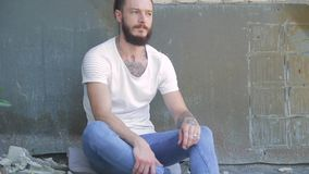 Przystojny brutalny mężczyzna z brodą w cajgach i białej koszulce na tle szara budowa i ściana z cegieł zbiory