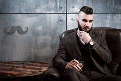 Przystojny brutalny młody elegancki brunetka mężczyzna z brodą siedzi w rzemiennym krześle na szarym tle, pije whisky zdjęcia stock