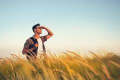 Przystojny caucasian mężczyzny spojrzenie przy krajobrazem z plecakiem na jego brać na swoje barki na łące, czas iść podróżować zdjęcie royalty free