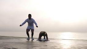 Przystojny caucasian mężczyzna w biel ubraniach ups z skokami w górę i piękną uśmiechniętą kobietą robi plunk ćwiczeniu robić pch zdjęcie wideo