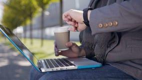 Przystojny caucasian młody człowiek ubierał w kurtce i szaliku siedzi na ławce z dalej, laptopem i kawa pisać na maszynie tekstem zbiory