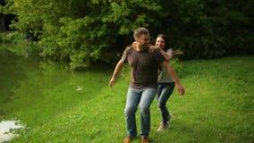 Przystojny chłopak niesie dziewczyny na jego z powrotem Romantyczna para ma zabawę podczas lato czasu przy miasto parkiem outdoor zbiory wideo