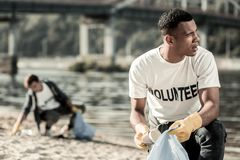 Przystojny ciemnowłosy uczeń jest społecznie aktywny podczas gdy czyścić plażę zdjęcia stock