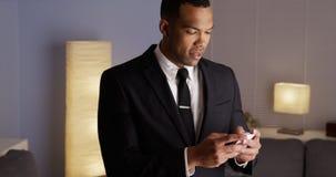 Przystojny czarny biznesmen pisać na maszynie na smartphone Zdjęcie Stock