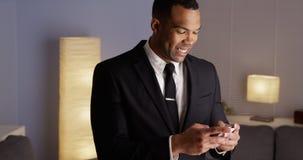 Przystojny czarny biznesmen pisać na maszynie na smartphone Obrazy Royalty Free