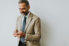 Przystojny dojrzały biznesmen z telefonem komórkowym w biurze Zdjęcia Royalty Free