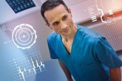 Przystojny doktorski ono uśmiecha się i jest ubranym błękita mundur przy pracą obrazy stock