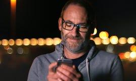 Przystojny dorośleć mężczyzna mówienie na mądrze telefonie przy jesień zmierzchem wewnątrz Obrazy Stock