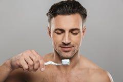 Przystojny dorośleć mężczyzna szczotkuje jego zęby Zdjęcia Royalty Free