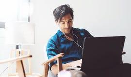 Przystojny dorosły mężczyzna pracuje w domu Obsługuje używać współczesnego laptop i hełmofony w rocznika krześle podczas gdy sied Obrazy Stock